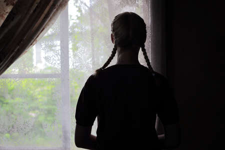 distinct: Girl with two distinct braids standing at the window