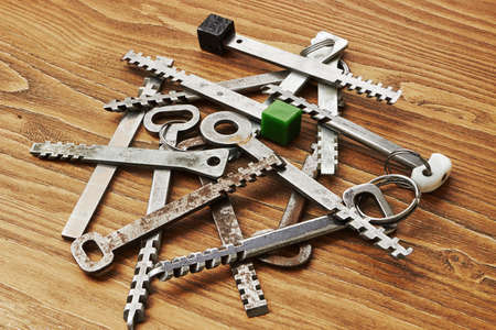 transom: Heap of transom (rack and pinion) the keys to the door on wooden background Stock Photo