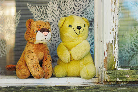 sill: Two soft toys on the window sill of rural house