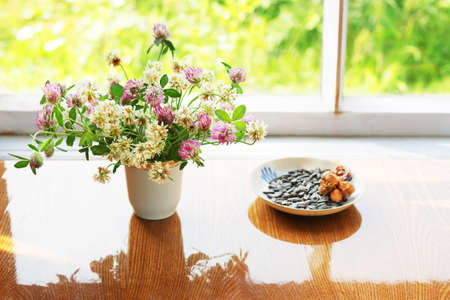 clovers: Bunch of clovers, sunflower seeds and hazelnuts Stock Photo