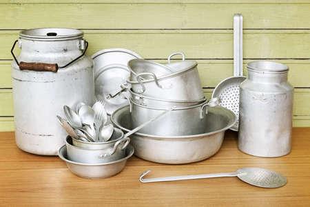 Old aluminum kitchen utensils are saucepans, dish, spoons, folks Banco de Imagens