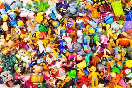 Heaps of the different small toys including Kinder Surprise as a background