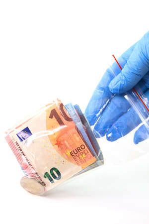 A hand in a medical glove holds a transparent plastic bag with money that is a source of infection. 免版税图像