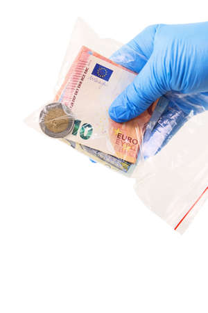 A hand in a medical glove holds a transparent plastic bag with money that is a source of infection. Isolated on white background
