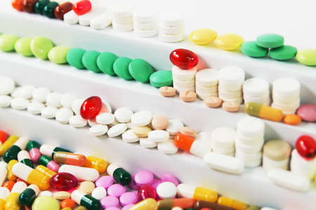 Many various medical pills in rows on stairs