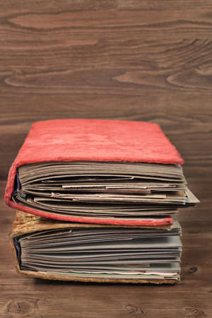 Two vintage thick photoalbums in the plush covers with text space on wooden background