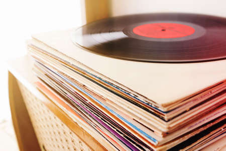 Pile of the vinyl records on the vintage radio player
