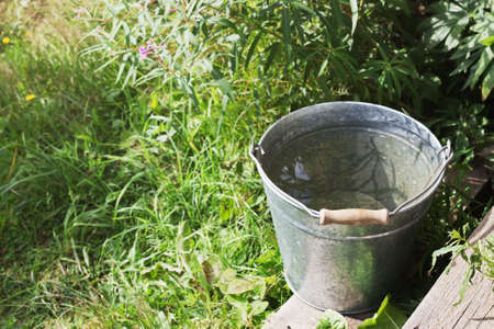 Metal bucket with the pure water in the summer