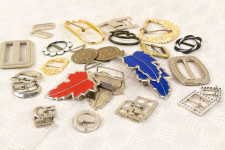 Various buckles old and new for clothes and footwear on the vintage cotton fabric