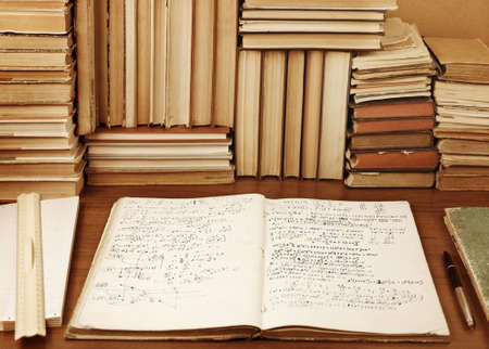 Writing-book with mathematical task solution against a background of books
