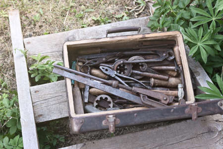 Various hand metal tools in the old suitcase on the wooden staircase outdoors 免版税图像