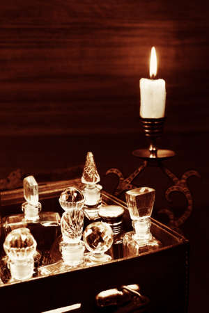 Candlelight in the bronse candlestick and vintage perfume crystal bottles in box 免版税图像