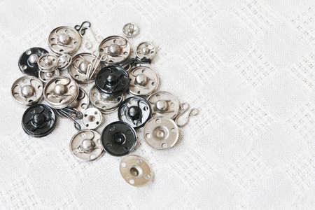 Group of various metal snap-fastenes and hooks on the vintage cotton fabric and text space