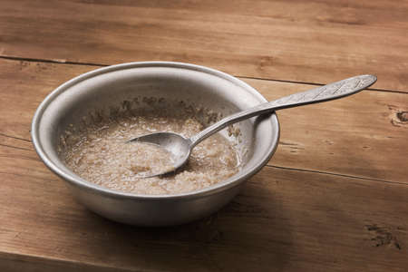 Grain porridge on water in the old aluminum bowl on the wooden table 免版税图像