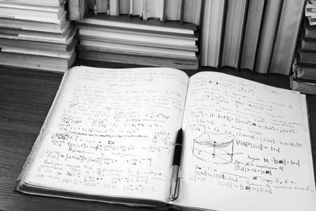 Open writing-book with mathematical lectures against a background of books 免版税图像