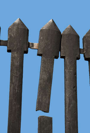 Broken cast iron vintage fence of a fortress isolated on blue