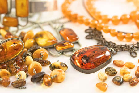 Various amber jewelry and other amber goods isolated on white background