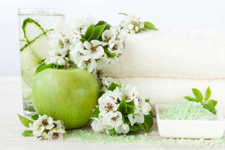Blossoming apple tree flowers, cold drink, green apple, aromatic sea salt and towels. Concept for spa, beauty and health salons. Close up photo on white wooden background, selective focus