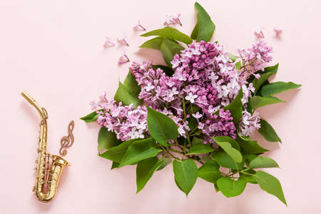 Little Golden saxophone and Bouquet of fresh fragrant pink lilac on pink paper background. Top view, close-up