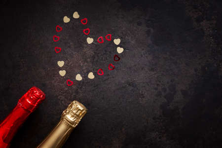 Two bottles of champagne and pattern of red and gold hearts. Top view, close-up, flat lay on dark brown background
