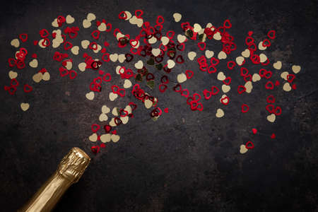 Bottle of champagne and pattern of red and gold hearts. Top view, close-up, flat lay on dark brown background