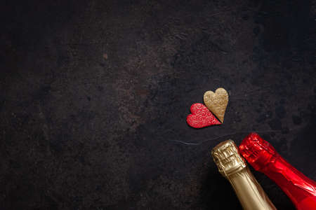 Two bottles of champagne and two hearts simbols. Top view, close-up, flat lay on dark brown background Stockfoto