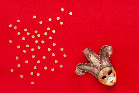 Venetian mask with heart shape gold glitter confetti. Top view, Close up on red background