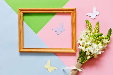 Close-up of the bouquet of white spring flowers, wooden frame and silhouettes of butterflies on the Pastel Candy Colours Background.  Happy Mother's Day, Women's Day, Valentine's Day or Birthday concept.  Floral flat lay minimalism geometric patterns greeting card. Archivio Fotografico