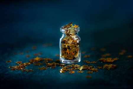 Gold glitter confetti in the small glass bottle. Close up on classik blue  background.