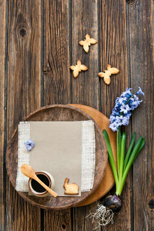 Close-up of a cute butterfly  cookies  and hyacinth flower on a vintage wooden background. Spring and Easter concept, top view, space for text. 免版税图像