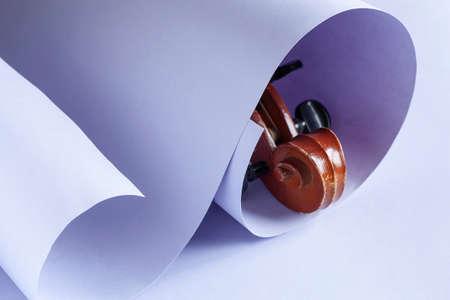 Violin curl fretboard in a paper scroll. Close-up, lilac colored paper