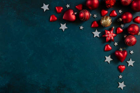 Christmas holiday background with red Christmas balls and silver stars on blue background. Close-up, top view, Christmas and New Year concept