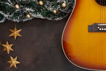 Acoustic guitar and Christmas garland decor with golden Christmas stars on dark brown background