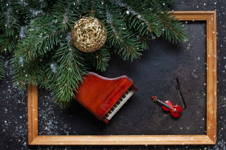 Miniature copies of the piano and violin with Christmas decor and snowflakes. Christmas, New Year's concept. Top view, close-up, wooden frame. Stock Photo