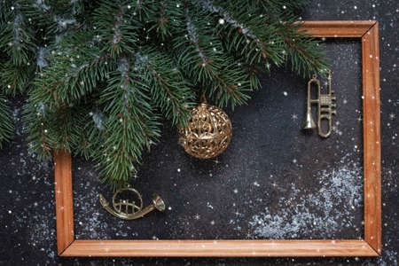 Christmas background with fir tree branches, Christmas decoration - stars, balls, trumpets, garland and wooden frame. Top view, close up Stock Photo