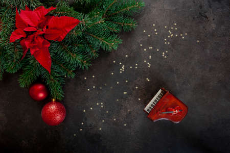 Miniature copies of the piano and violin with Christmas decor and poinsettia. Christmas, New Year's concept. Top view, close-up