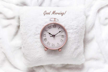 Pink alarm clock on a white pillow on a white blanket. Good morning love concept Zdjęcie Seryjne
