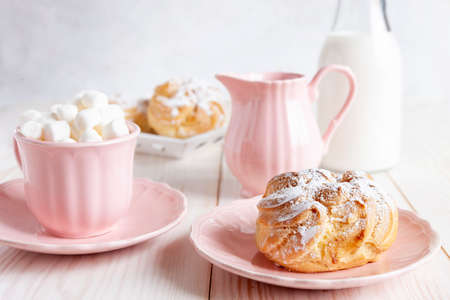 Close-up of fresh cream buns and pink cup with hot drink and marshmallows on a white background. Good morning love concept Zdjęcie Seryjne
