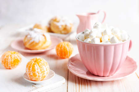 Close-up of pink cups with hot drink and marshmallows, fresh tangerines and cream buns on a white background. Good morning love concept