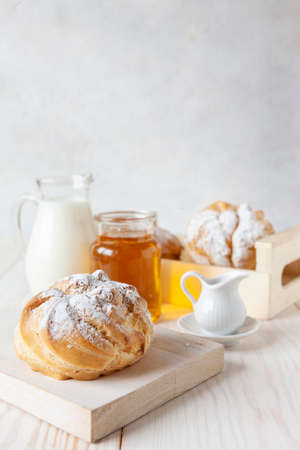 Close-up of cream buns, bottle of milk and honey on a white background. Good morning love concept Zdjęcie Seryjne