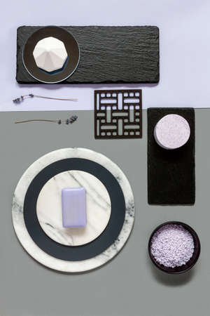 Modern trendy SPA and wellness concept with lavender bath salt and soap on natural stones plates. Close up, top view on neutrals tones paper background