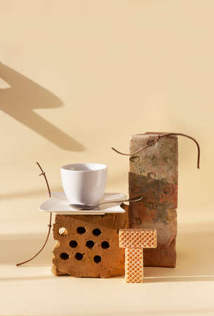 Trendy still life with old bricks, dried plants, a cup of coffee and cookies. Previously used objects in modern living space. Zero Waste Principle