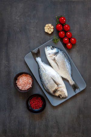 Fresh dorado fish with spices, garlic and seasoning on black cutting board on the table. Top view, copy space.