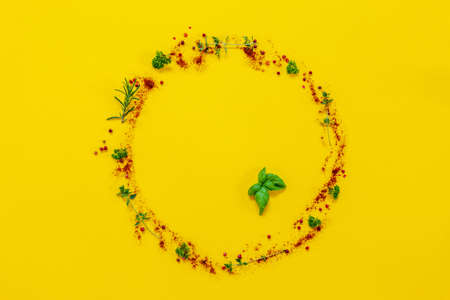 Seasonings on the table, poured into a round plate on the yellow background