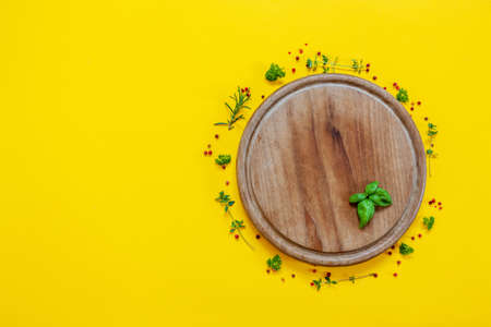 Seasonings on the wooden circle cutting board on the yellow background