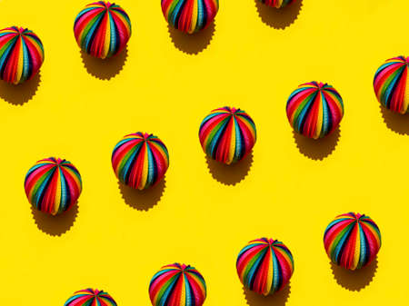 Geometric pattern of Rainbow Sphere on a bright yellow background, top view