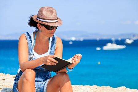 Donna lettura di un libro sulla spiaggia. Archivio Fotografico