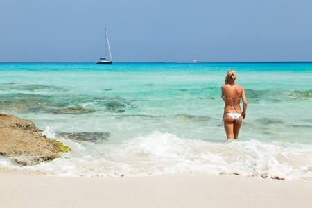 formentera: Young woman with cellphone on the beach.