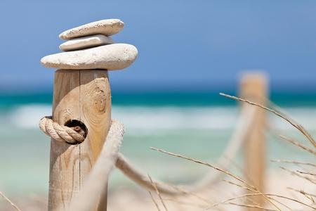 Pietre in equilibrio sulla ringhiera di legno vicino alla spiaggia.