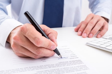 policy document: Businessman signing a document  Stock Photo